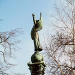vrouwenfiguur met gespreide armen en wapperende vlag als symbool van de vrijheid